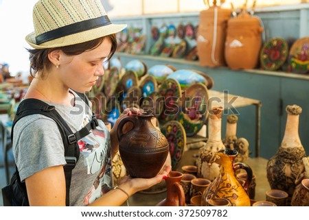 the young beautiful woman holds in hand a handwork jug on the Opening day in Armenia - stock photo