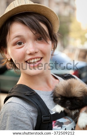 the young beautiful woman in a hat holds a little puppy in hand - stock photo
