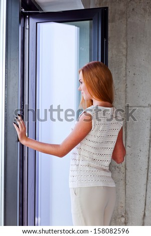 The young beautiful woman in jersey before a window