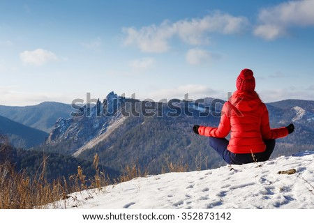 The young beautiful woman in mountains has a rest in the winter at the weekend, meditation, yoga - stock photo