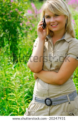 The young beautiful woman speaks by a mobile phone in city park.