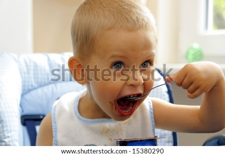 The young boy feed himself with spoon - stock photo