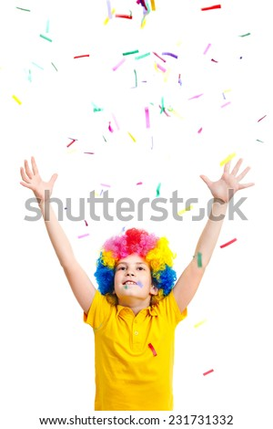 The young boy in clown wig throws colored confetti, isolated on white background - stock photo
