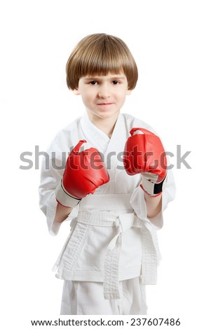 The young boy in white kimono and boxing gloves, isolated against white background - stock photo