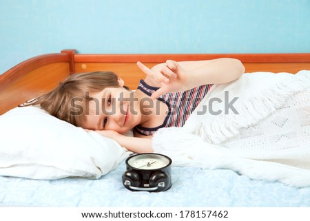 The young boy lay in bed with alarm clock - stock photo