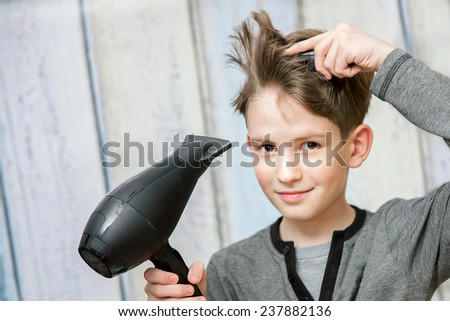 The young boy with black blow dryer  - stock photo