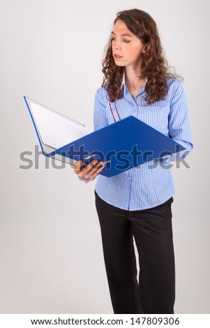 The young business woman is reading in a file - stock photo