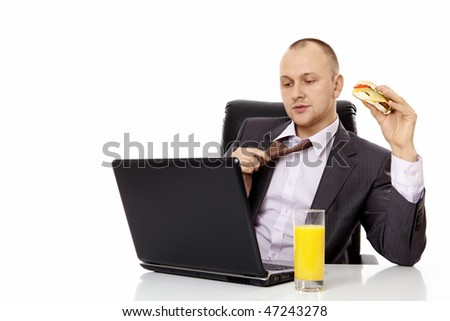 The young businessman has a bite behind the laptop - stock photo