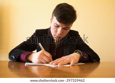 The young businessman signs the documents - stock photo