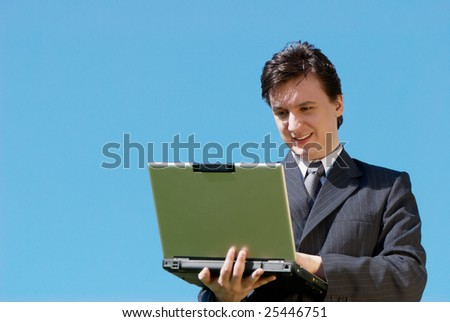 The young businessman with laptop against sky
