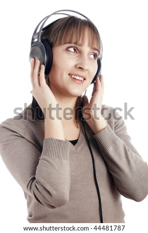 The young charming smiling girl listens to music in ear-phones