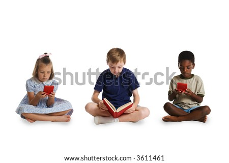 The young children of different races sitting together - two playing electronic games and the third reading a book. This image is one of a series of conceptual images isolated on white backgrounds. - stock photo
