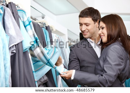 The young couple considers clothes in shop - stock photo