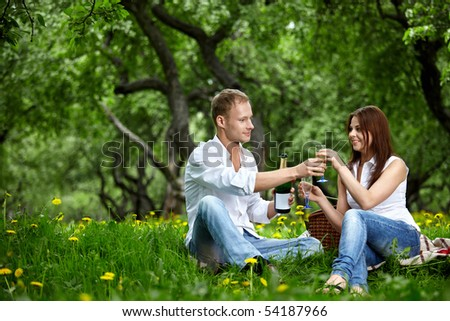 The young couple drinks champagne in wood - stock photo