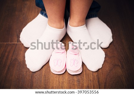 The young couple legs between with their baby's shoes - stock photo