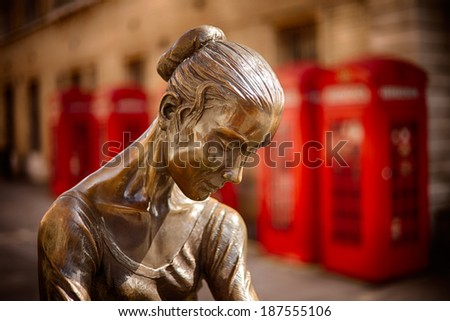 The Young Dancer Enzo Plazzotta's bronze statue opposite the Royal Opera House, home of the Royal Ballet against red phone boxes - stock photo