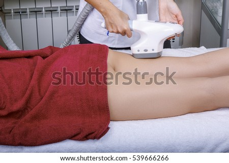 The young dark-haired woman in the office of the hardware correction to vacuum massage procedure
