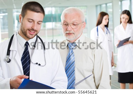The young doctor talks to the patient - stock photo
