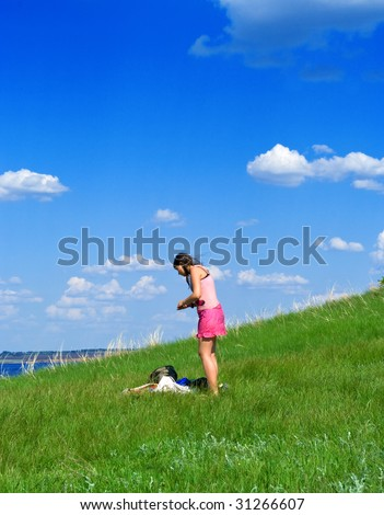 The young girl against summer landscape with cloudy sky