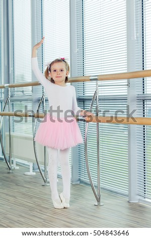 The young girl dances in a ballet tutu in the hall