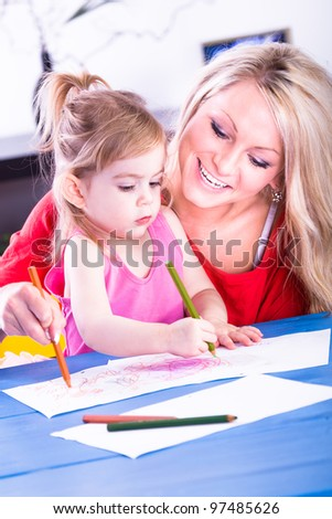 the young girl drawing with her mother