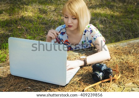 The young girl has a rest in park with the computer - stock photo