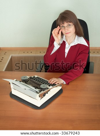 The young girl in office armchair with typewriter