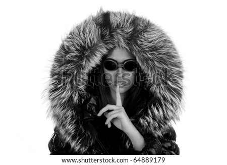 The young girl in sunglasses and a fur hood, to symbols silence ( black white ) - stock photo