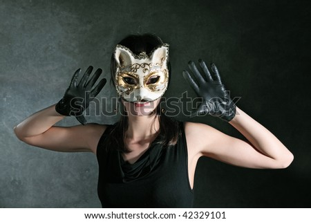 The young girl in the Venetian mask of a cat against a dark background