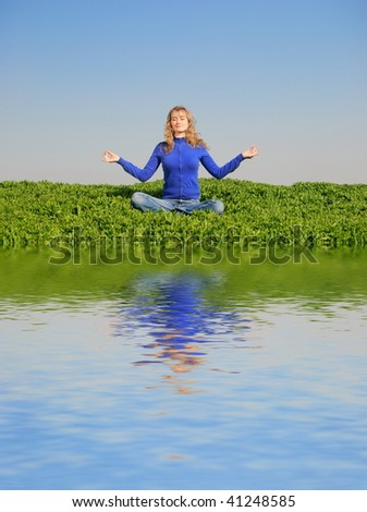The young girl meditates in a spring field - stock photo