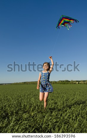 The young girl quickly runs on a green glade with kite,  happy smiles - stock photo