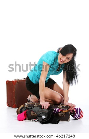 The young girl tries to place clothes in an old suitcase