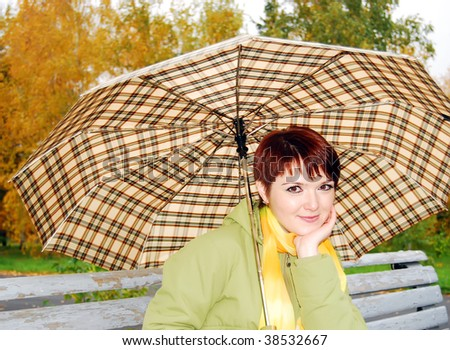 The young girl under an umbrella on an old bench. - stock photo