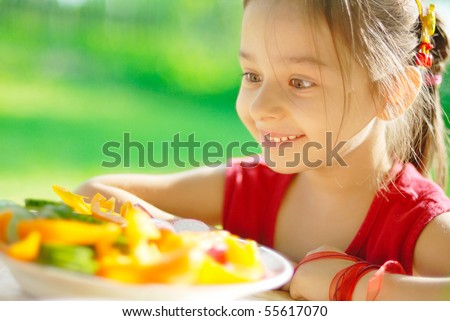 The young girl was delighted, that to it have given a plate of the cut vegetables - stock photo