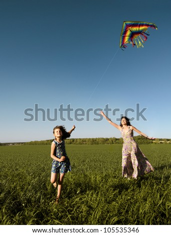 The young girl with  mother quickly runs on a green glade ,  fly a kite and happy smiles - stock photo