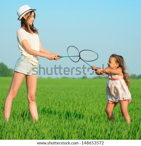 The young girls plays with a racket in badminton over green grass - stock photo