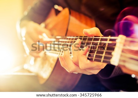 the young guy playing an acoustic guitar. Shooting backlit - stock photo