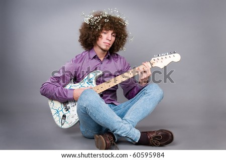 The young guy with curly hair and a guitar in hands. - stock photo
