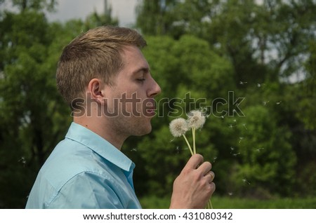 the young handsome man blowing on a dandelion