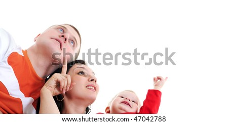 The young happy family looks and shows upwards - stock photo