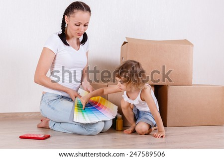 The young happy mother and daughter sit in a room on the floor with a color guide near a lot of the boxes. Moving, purchase of new habitation or repair of a room. - stock photo