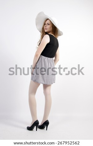 The young long-haired blond woman in French style, with a large hat and short dress - stock photo