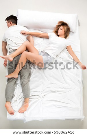 The young lovely couple lying in a white bed, love lconcept, top view
