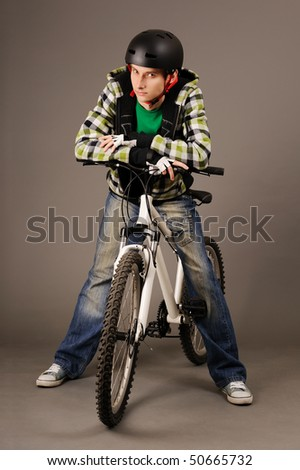 The young male bicyclist with bicycle on grey, studio shot. - stock photo