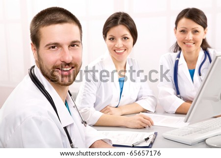 The young male doctor and its colleagues - stock photo