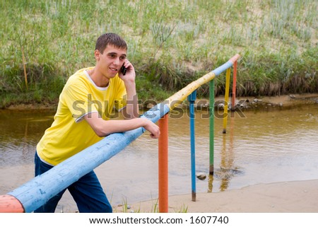 The young man and mobile. At the small river. - stock photo