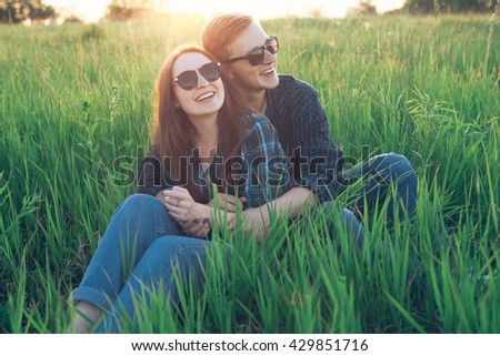 The young man and the girl sitting on the grass