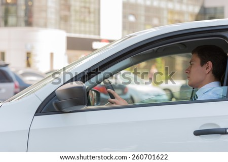 The young man behind the wheel driving car - stock photo