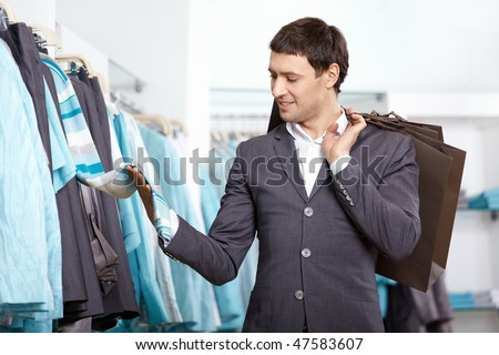 The young man chooses clothes in shop