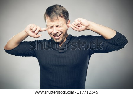 The young man closed ears - stock photo